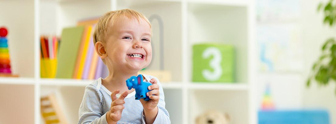 Niño sonriendo con un juguete en las manos