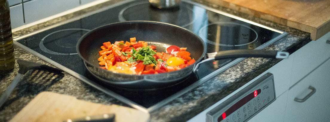 Sartén con verduras y huevo sobre una vitrocerámica.