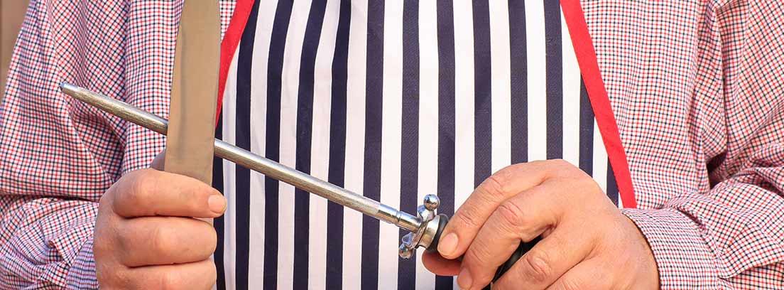 Hombre con mandil afilando un cuchillo con un chaira