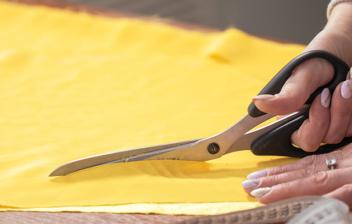 Mujer cortando tela de color amarillo