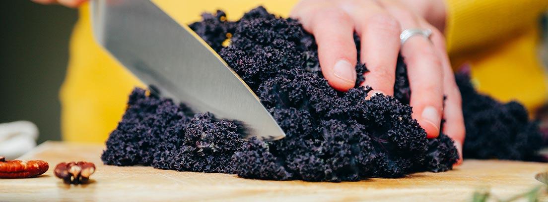 Mano con un cuchillo cortando sobre una tabla kale.