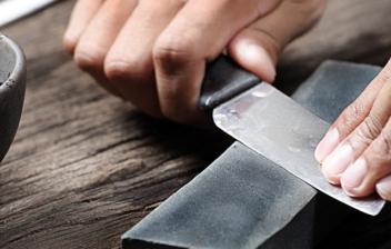 Manos afilando un cuchillo sobre una piedra de afilar.