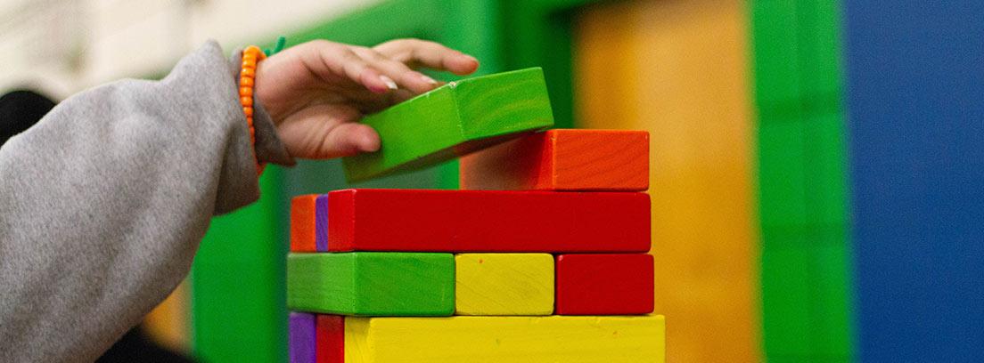 Mano de niño poniendo pieza de madera en torre de bloques de colores