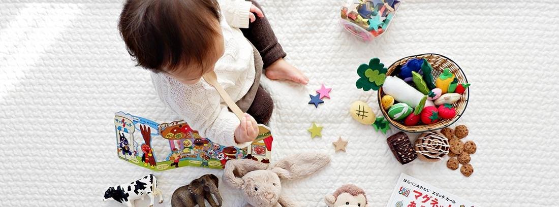 Niño pequeño sentado en el suelo rodeado de juguetes