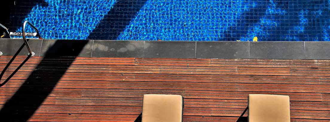 Dos tumbonas junto a una piscina
