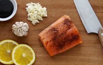 Lomo de salmón junto a dos rodajas de limón y un cuchillo sobre una tabla de madera