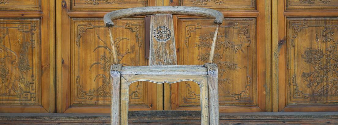 Silla de madera delante de una puerta antigua
