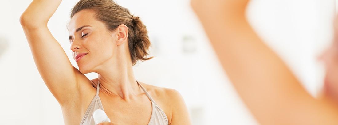 Mujer con brazo levantado y desodorante en la mano para aplicar