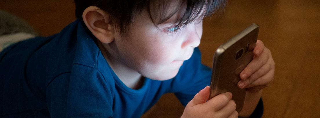 Niño mirando la pantalla de un teléfono móvil