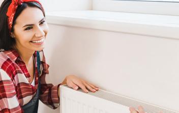 Mujer comprobando la temperatura del radiador