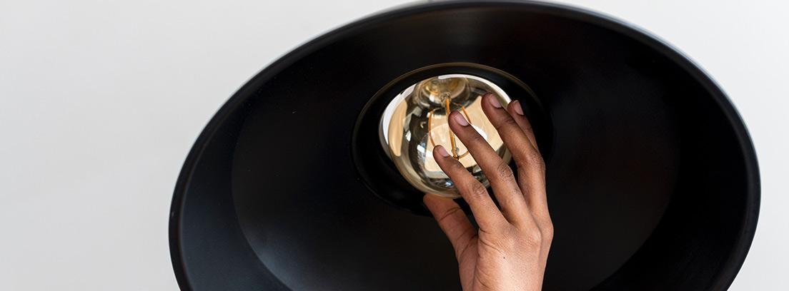 Manos de mujer poniendo una bombilla en una lámpara de techo