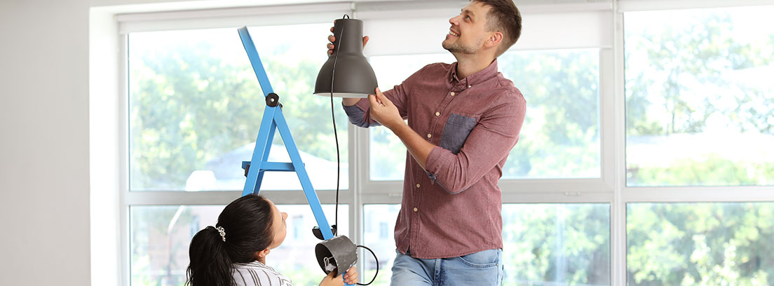 Mujer junto a un hombre subido a una escalera para colgar una lámpara