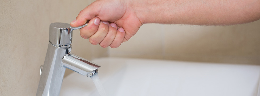 Mano abriendo el grifo de un baño