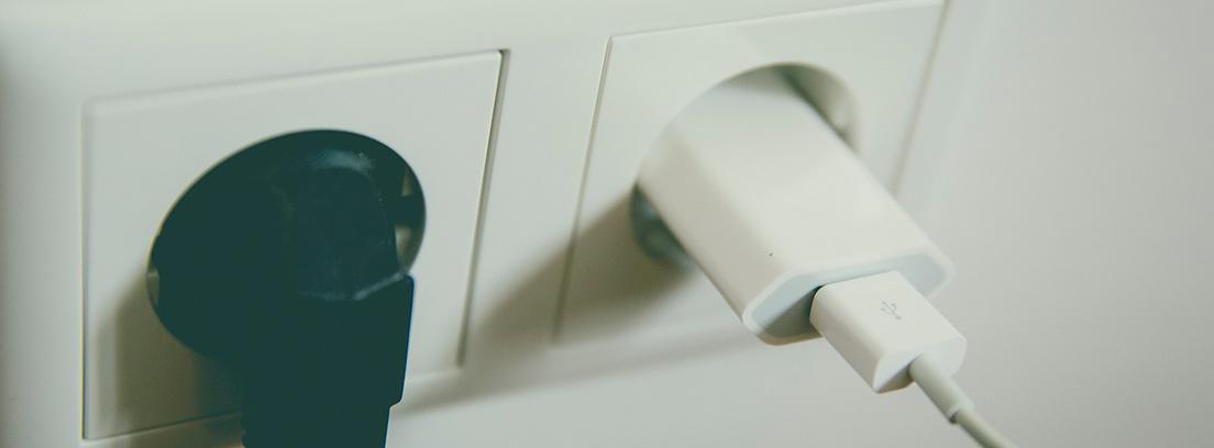 : Dos enchufes de pared uno con cable negro y otro con cargador blanco.