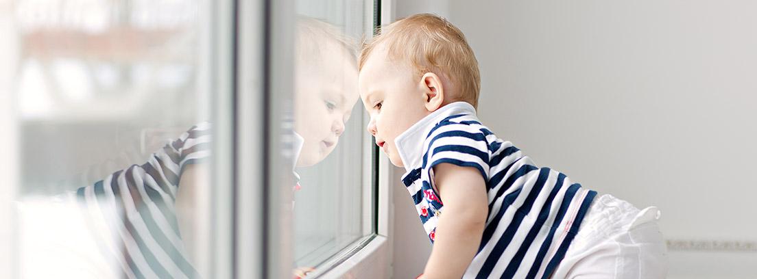 Bebé asomándose a una ventana de aluminio blanco