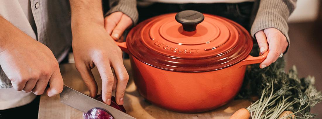 Manos cortando cebolla junto a olla y zanahorias en una tabla.