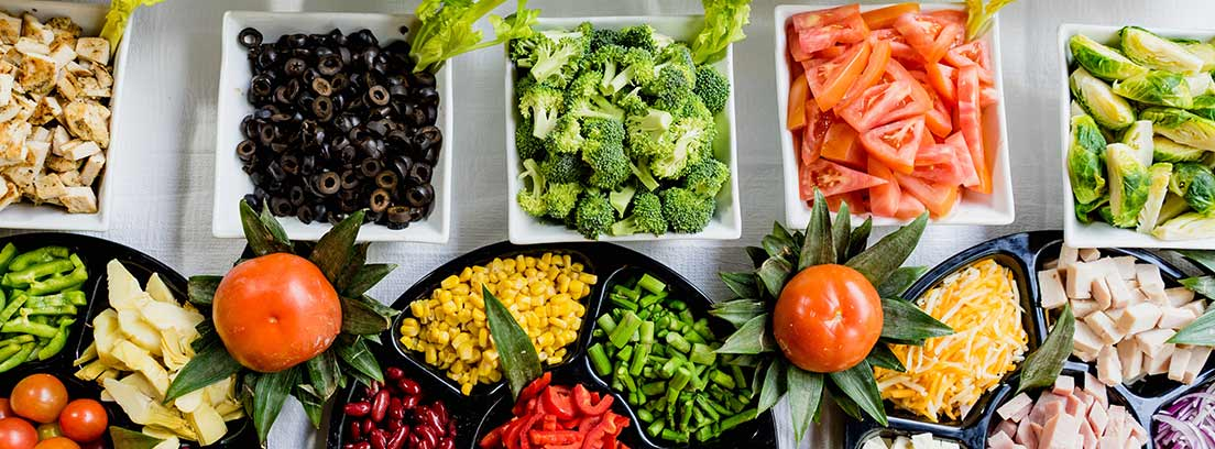 Platos y fuentes con muchas verduras y hortalizas cortadas y al natural.