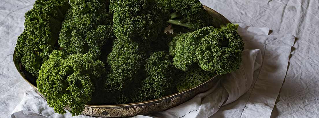 Brócoli crudo en una bandeja sobre mantel blanco