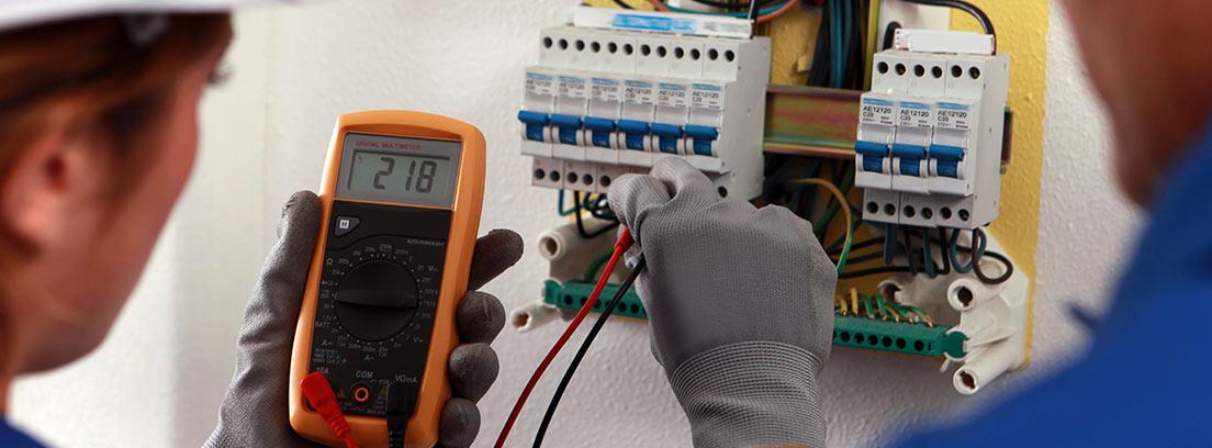 Electricistas usando un tester en un cuadro eléctrico