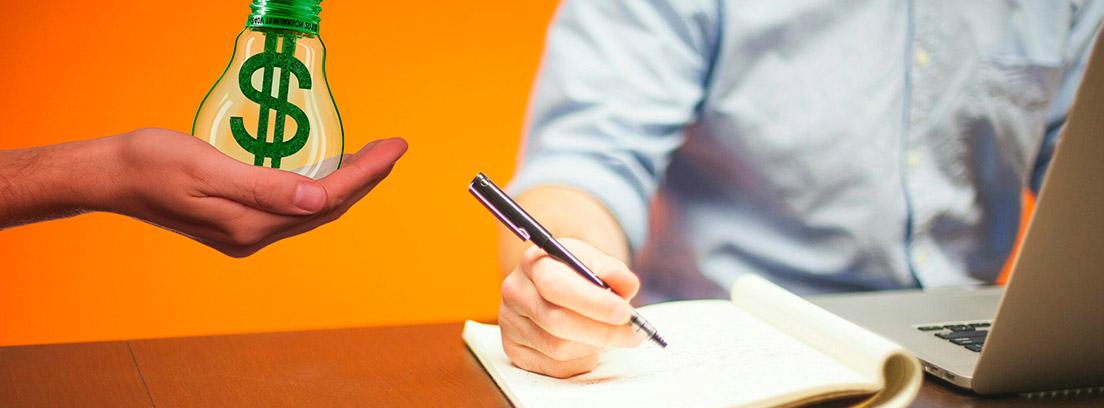 Hombre con ordenador escribiendo en un cuaderno y mano extendida sujetando una bombilla con el símbolo del dólar