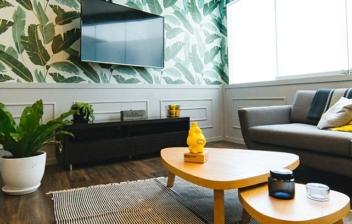 Salón con mesas amarillas y pared con hojas verdes.