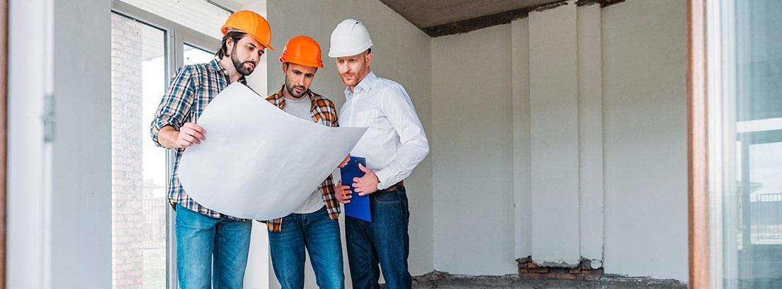 Tres hombres con casco mirando unos planos dentro de un edificio en obras