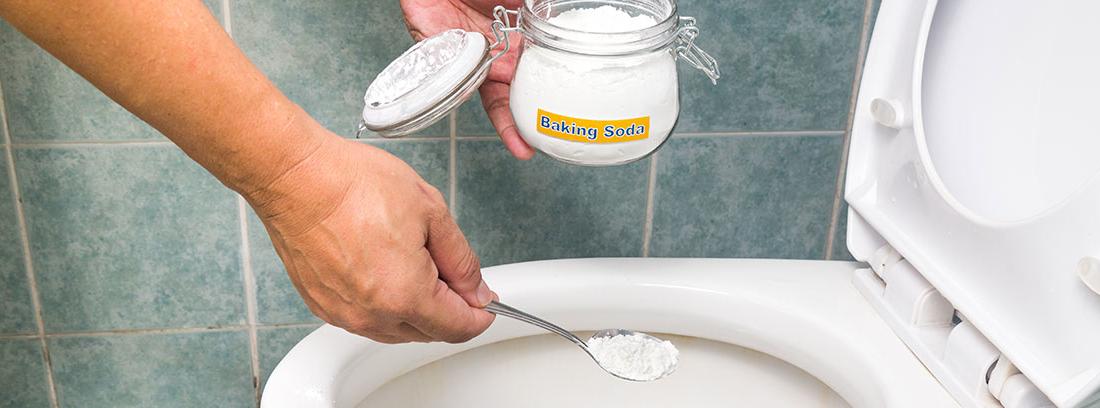 Mano echando bicarbonato con una cuchara en un inodoro.
