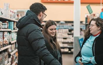 Un hombre y dos mujeres junto a carro de la compra en un pasillo de supermercado.