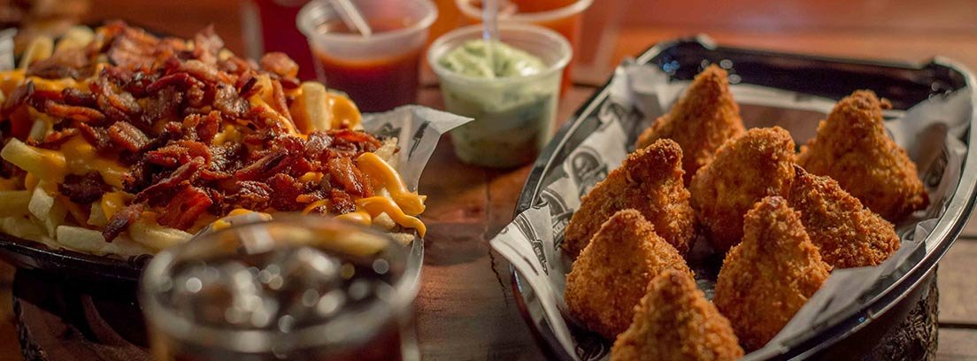 Mesa con salsas, bebida y comida empanada.