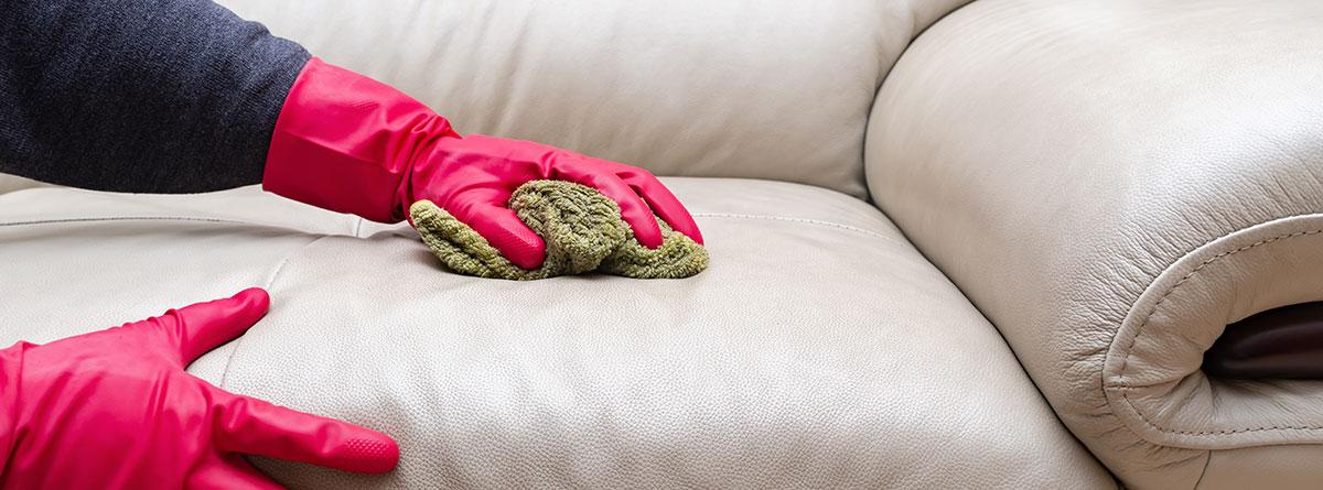 Manos con guantes limpiando un sofá de cuero blanco