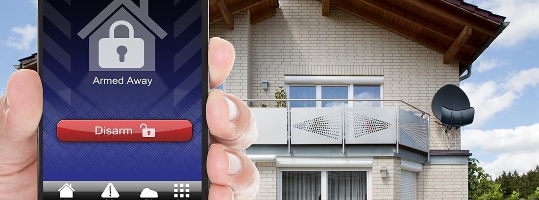 Mano sujeta móvil con pantalla de casa con candado delante de casa real.