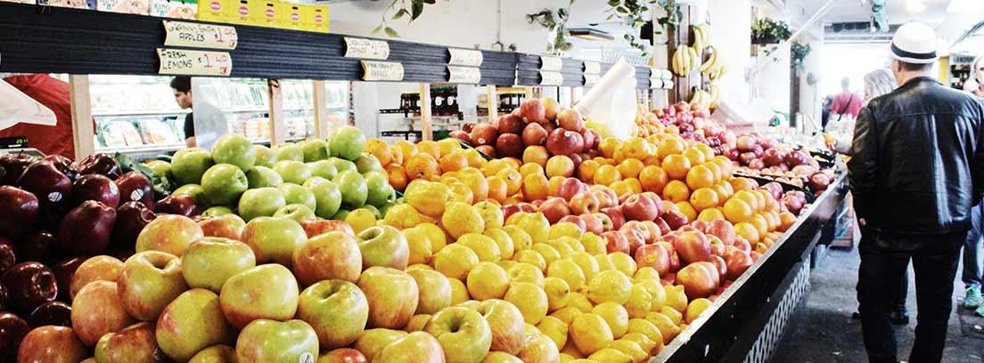 Puesto de frutería con manzanas y otras frutas.