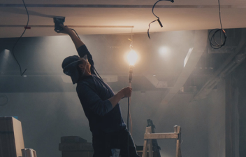 Hombre subido a escalera con mano en el techo de una habitación en obras.