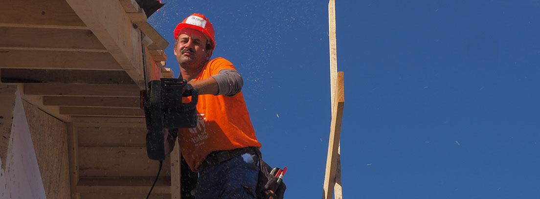 Hombre con casco rojo y máquina en la mano trabaja de madera.