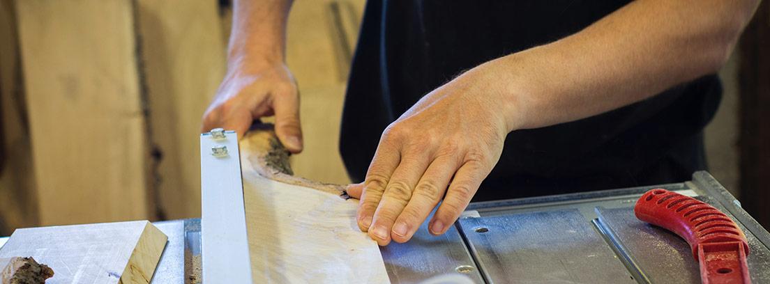 Manos sujetando trozo e madera junto a sierra de calado.