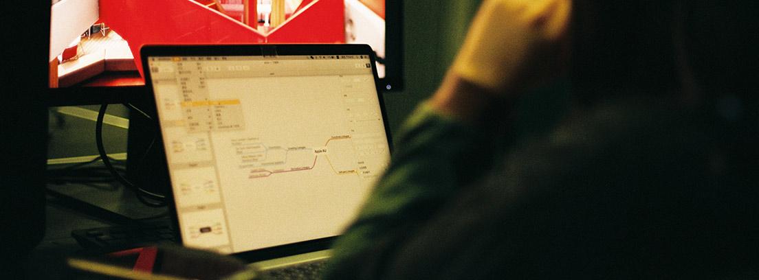 Mujer de espaldas sentada delante de ordenador portátil y monitor grande.
