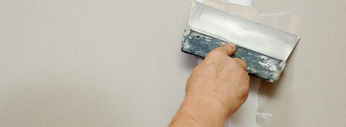 Mano con espátula aplicando masilla en una pared