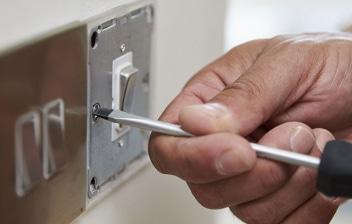 Manos cambiando un interruptor de luz