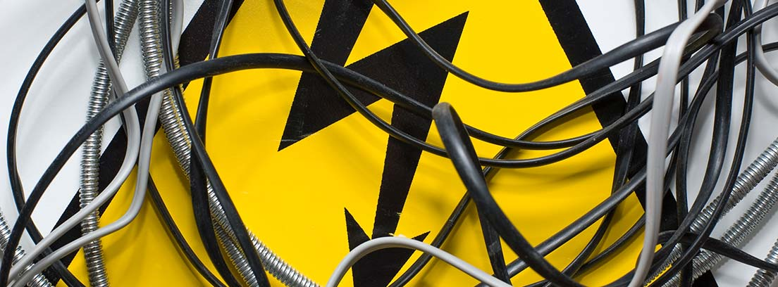 Cables sobre distintivo amarillo con rayo negro sobre él.