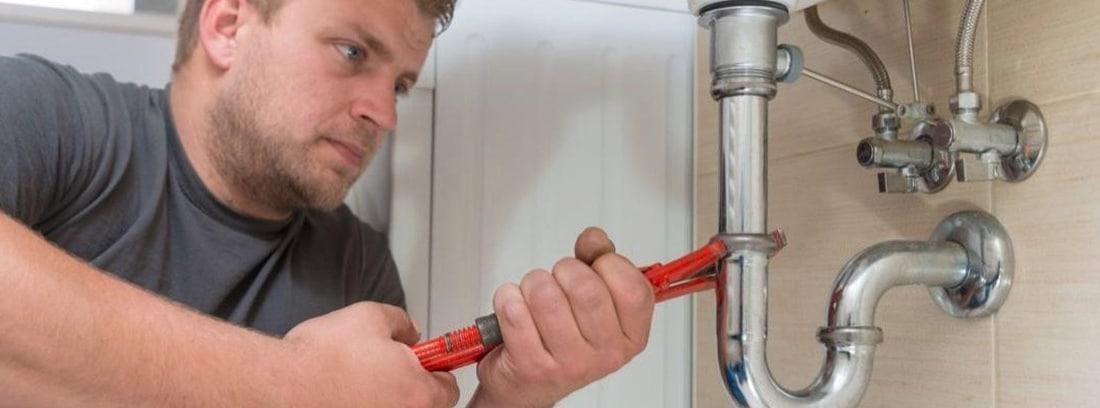 Hombre trabajando para limpiar la cal de una tubería