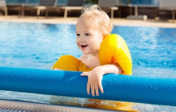Niño dentro de una piscina sujetándose en un enrollador de cubiertas para piscina