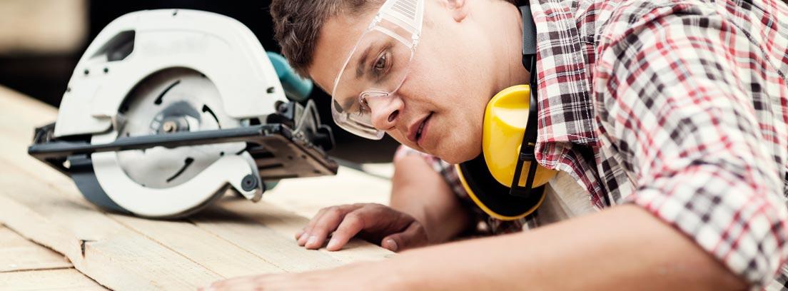 Hombre con gafas de protección y mano sobre tablón de madera junto a sierra circular.