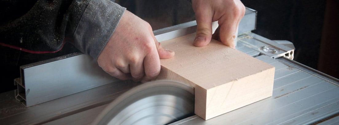 Manos sujetando madera que pasa por una sierra redonda en mesa.