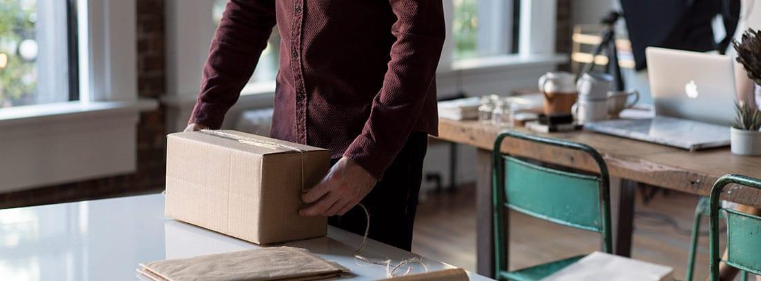 Hombre preparando paquete en una caja y sobre una mesa