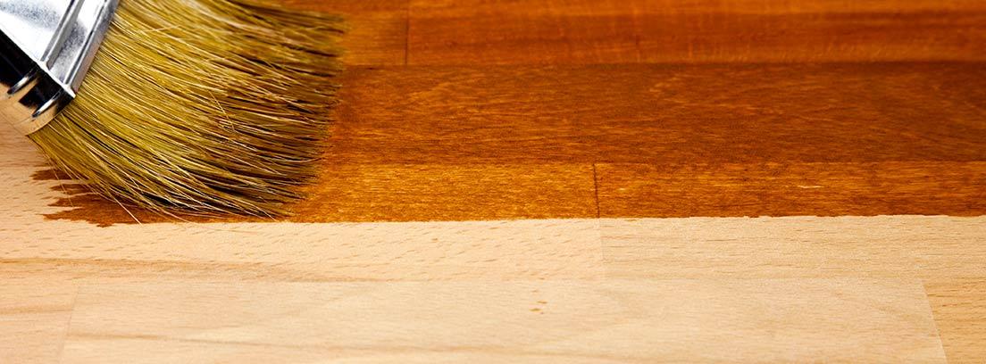 Brocha aplicando barniz sobre una tabla de madera