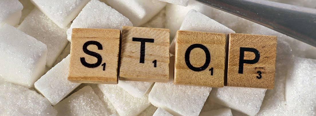 """Letras Scrabble formando la palabra """"stop"""" sobre terrones de azúcar"""