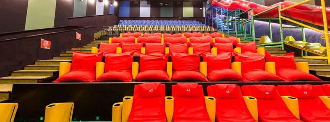 Sala junior de cine con asientos y tumbonas naranjas instalados en filas