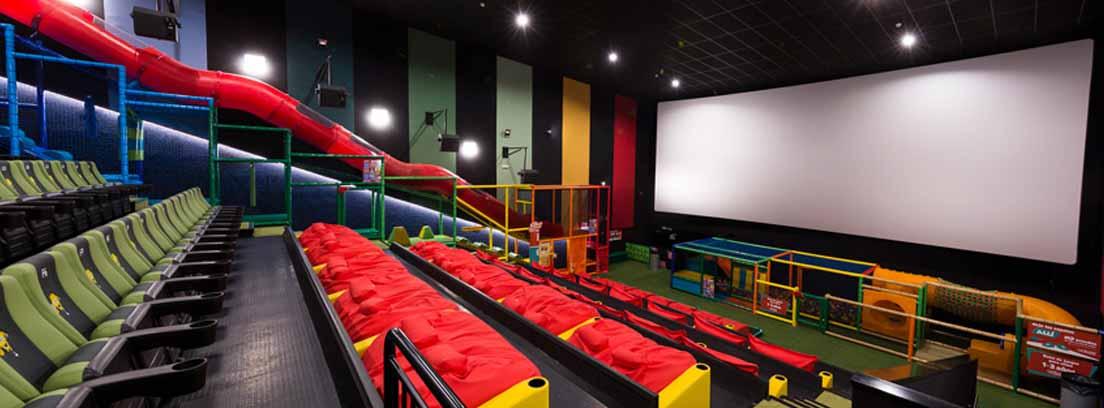 Salas junior de cine con butacas verdes y rojas y tobogán en forma de tubo.