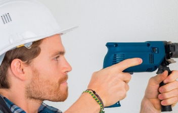Hombre con un taladro haciendo un agujero en un muro de carga