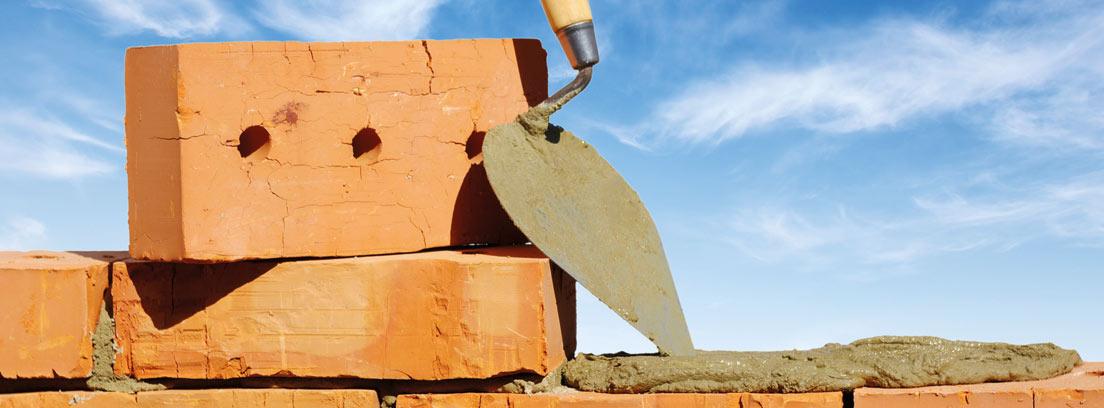 Paleta de albañil sobre pared de ladrillos a medio hacer